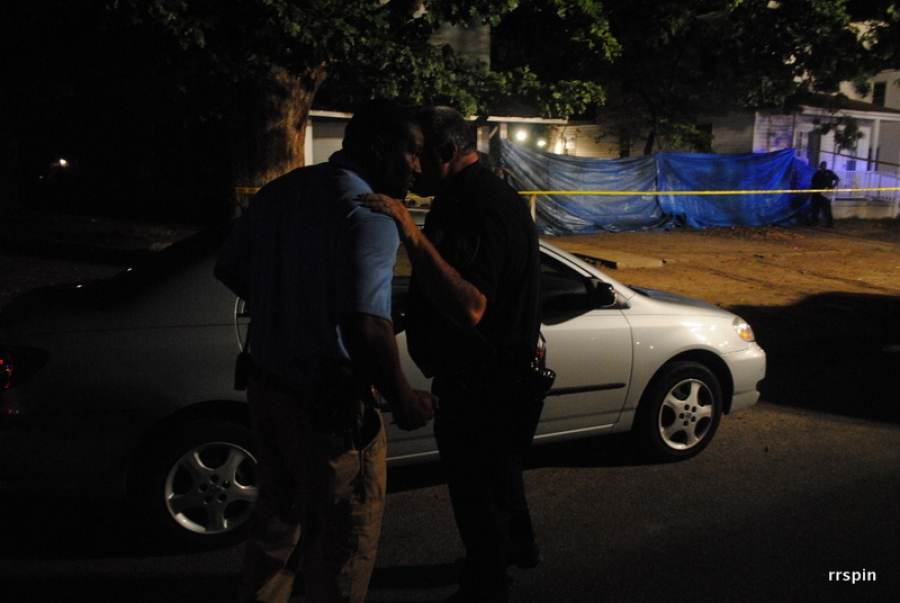 Detective Corey Dixon, left, and Officer Mark Peck confer at the murder scene.