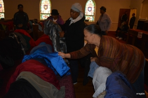 A church member, foreground, sorts the coats as a guest examines one.