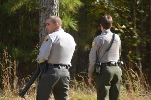 An armed trooper and park ranger stand watch at the perimeter.