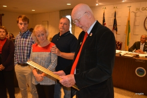 Manning reads the framed resolution to Isles, as her husband, David, stands behind her for support and their son, Sammy, and Hux's sister, Joan Webster, look on.
