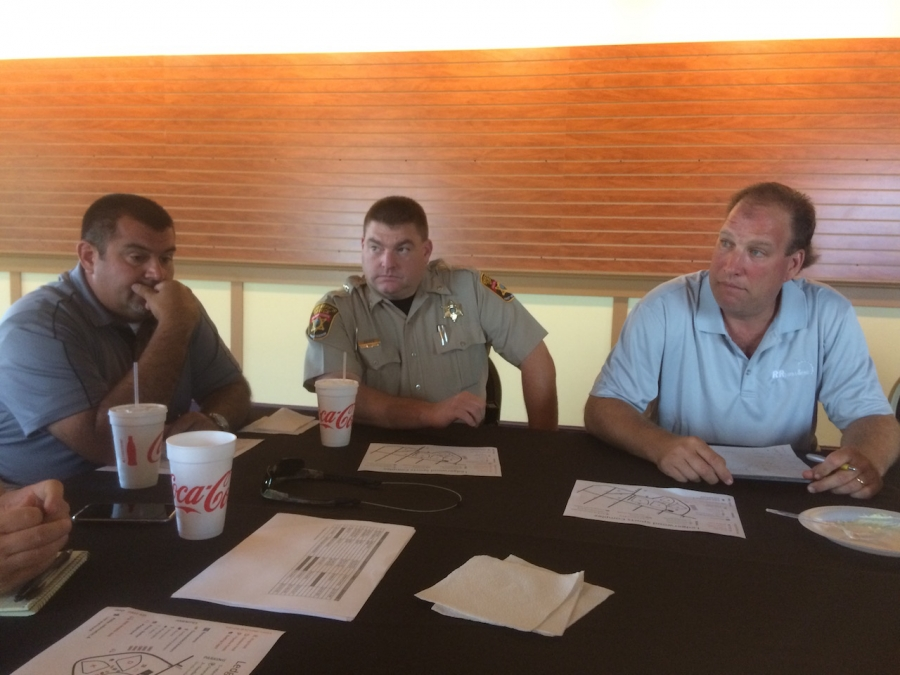 From left, Hall and Major Neil Aycock and Roanoke Rapids Parks and Recreation Director John Simeon discuss plans for the tournament with other officials today.