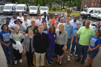 Letter carriers surround the beneficiaries of the food drive and mayors.