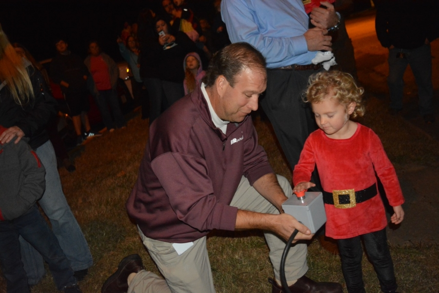 Parks and recreation Director John Simeon holds the box as Madelyn presses the button to light the tree.