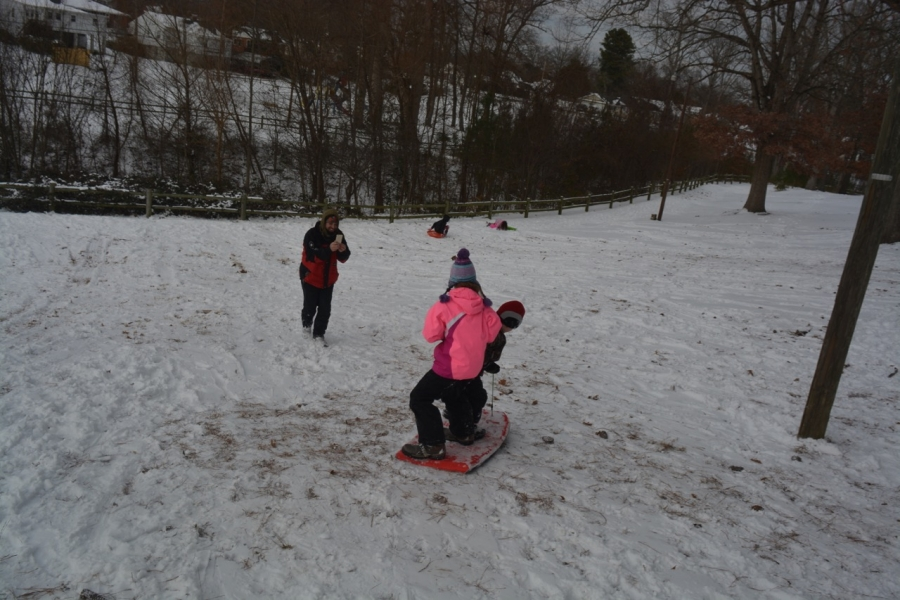 Children and parents frolic in the snow at T.J. Davis this afternoon.