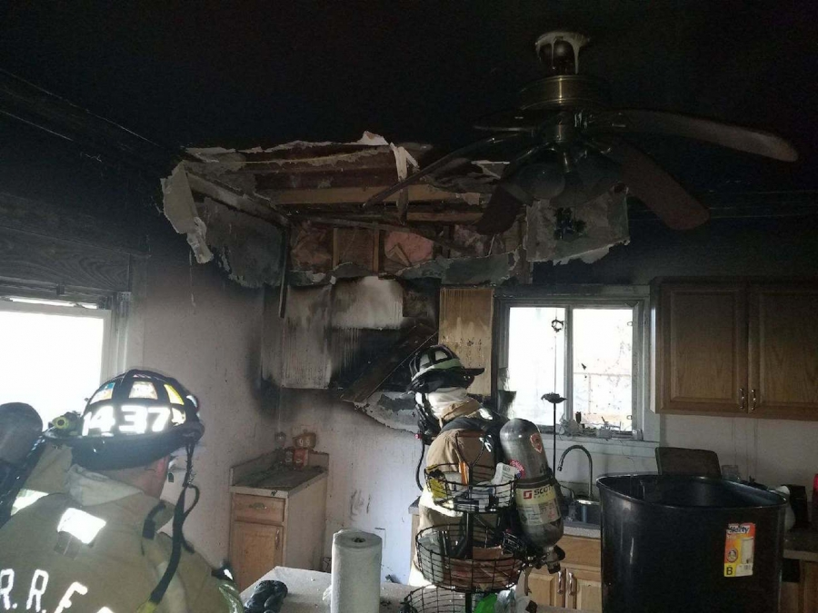 Firefighters examine the kitchen after the blaze.