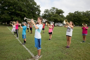 The brass section practices at Aker's Field.