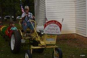 A tractor pulling cars for children and adults makes its way around the 4H Rural Life Center.