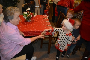A child hands a resident a bag of cookies.