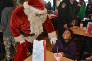 A child laughs with Santa during breakfast at Chick-fil-A before the Walmart shopping spree.