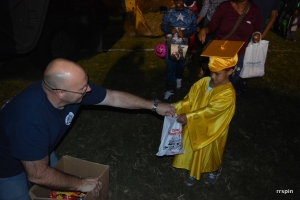 Roanoke Rapids police Chief Chuck Hasty hands out candy to a child dressed as a graduate this evening.