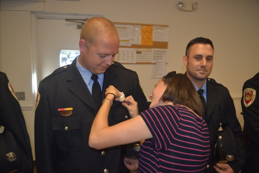 Jayme Jenkins pins the badge on her husband.